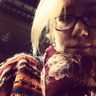 Sad hipster at the bus stop on a cold rainy night.